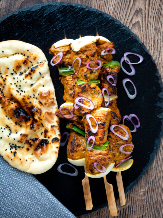 Overhead lamb tikka kebabs with onion and green pepper served with a naan bread.