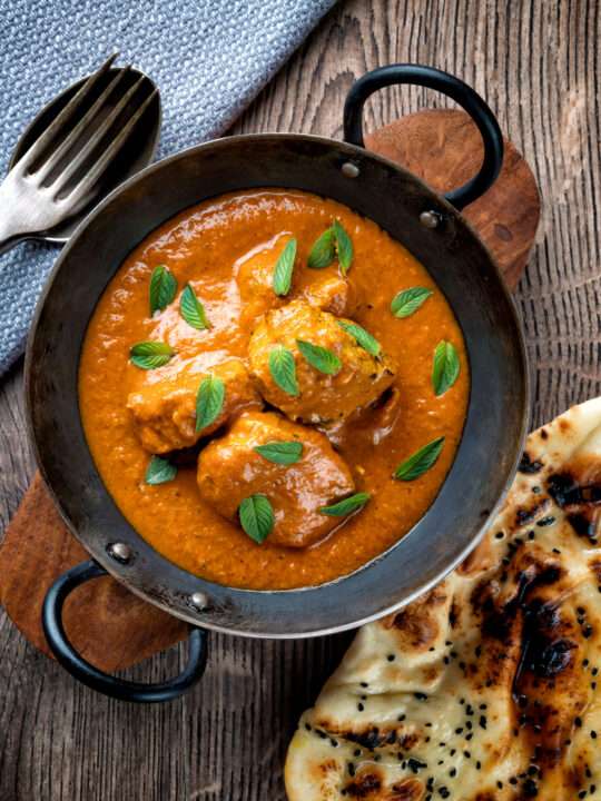 Overhead Indian lamb tikka masala curry served with a naan bread.