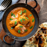 Overhead Indian lamb tikka masala curry served with a naan bread featuring a title overlay.