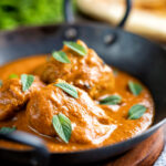 Indian lamb tikka masala curry served with a naan bread featuring a title overlay.