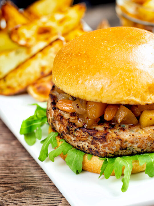 Pork and apple burgers served with rocket, chutney and a side of potato wedges.