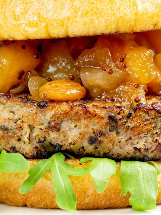 Closeup pork and apple burgers served with rocket, chutney.