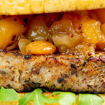 Closeup ork and apple burgers served with rocket, chutney featuring a title overlay.