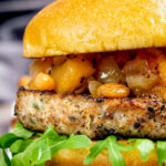 Pork and apple burgers served with rocket and apple chutney featuring a title overlay.