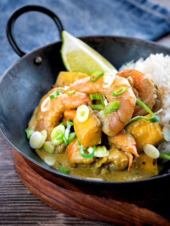 Prawn and mango curry with rice served in an iron karahi.