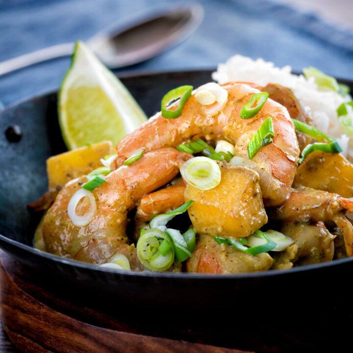Indian prawn and mango curry with rice served in an iron karahi.