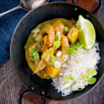 Overhead prawn and mango curry with rice and lime wedge served in a karahi featuring a title overlay.
