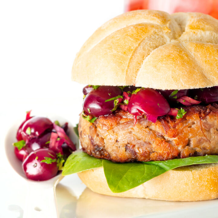 Close up shredded duck burgers topped with cherry salsa on a burger bun.
