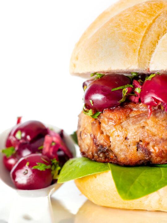 Shredded duck burgers topped with cherry salsa on a burger bun.