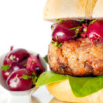 Shredded duck burgers topped with cherry salsa on a burger bun featuring a title overlay.