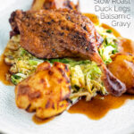 Slow roast duck leg with balsamic gravy, cabbage and roast potatoes featuring a title overlay.