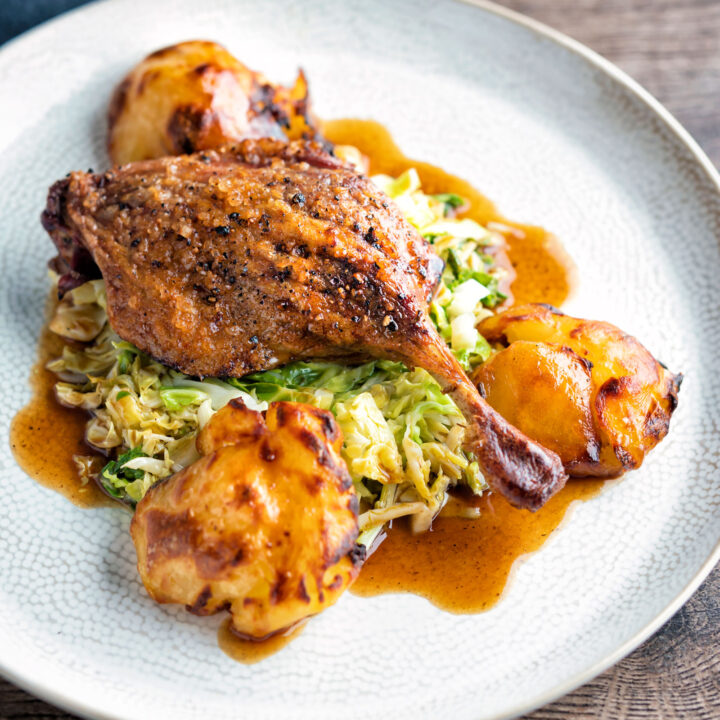 Slow roast duck legs served on cabbage with roast potatoes and balsamic gravy.