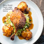 Overhead slow roast duck leg with balsamic gravy, cabbage and roast potatoes featuring a title overlay.