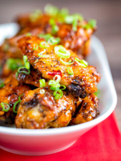 Close up sticky spicy Thai inspired chicken wings with green onion.