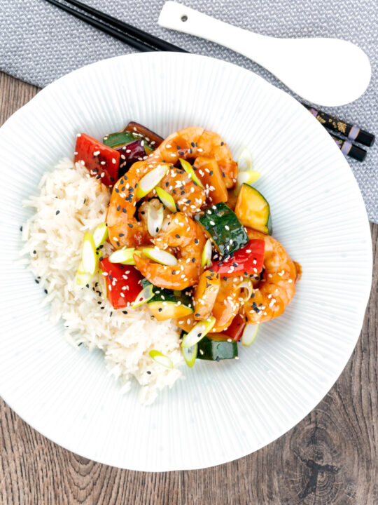 Overhead sweet and sour prawns or shrimp with vegetables and rice.