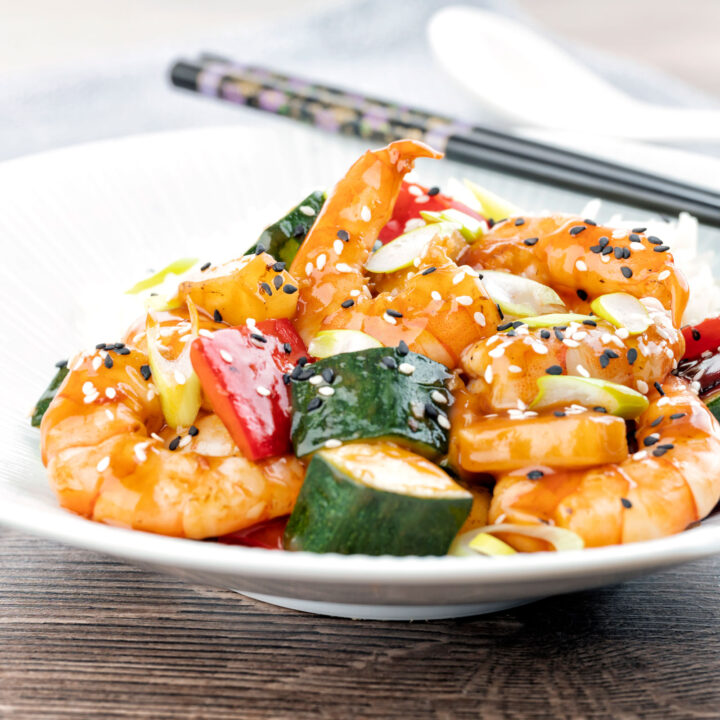 Sweet and sour prawns or shrimp with vegetables and rice in a white bowl.