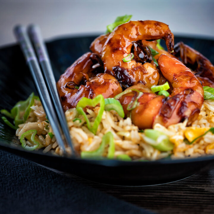 Teriyaki prawns served with egg fried rice and chopsticks on a dark plate.