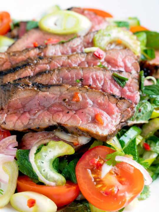 Close up Thai beef salad with rare beef, tomatoes, mint, chilli and cucumber.