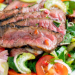 Close up Thai beef salad with rare beef, tomatoes, mint, chilli and cucumber featuring a title overlay.
