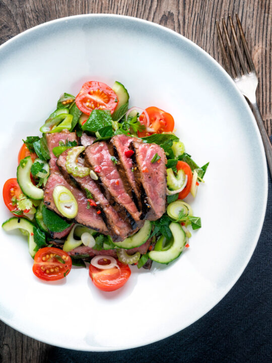 Overhead Thai beef salad with rare beef, tomatoes, mint, chilli and cucumber.