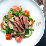 Overhead Thai beef salad with rare beef, tomatoes, mint, chilli and cucumber featuring a title overlay.
