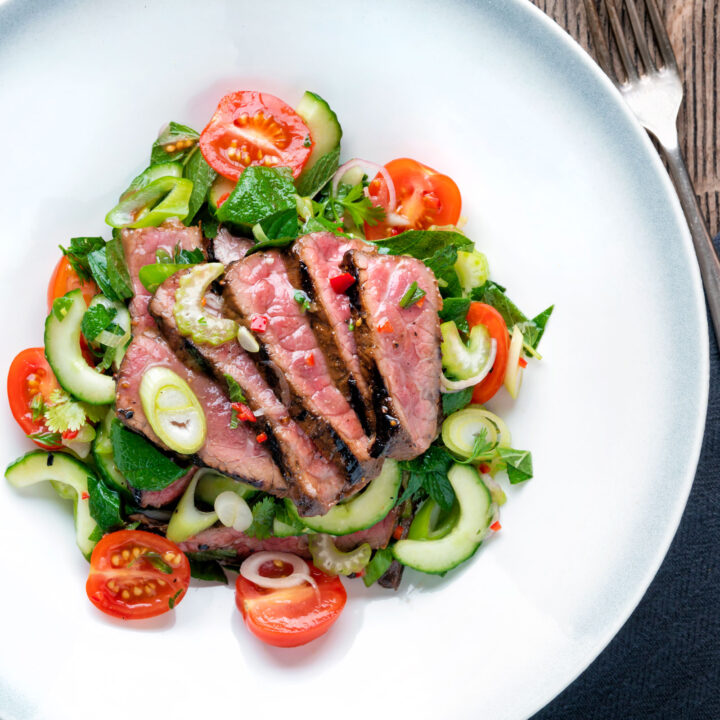 Overhead Thai beef salad with rare beef, tomatoes, mint, chilli, shallot, celery and cucumber.