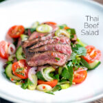 Thai beef salad with rare beef, tomatoes, mint, chilli, shallot, celery and cucumber featuring a title overlay.