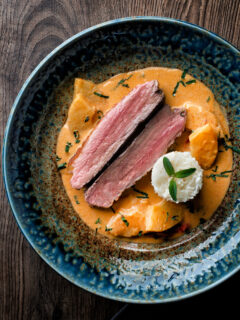 Overhead Thai red duck curry with pineapple, rice and Thai basil.