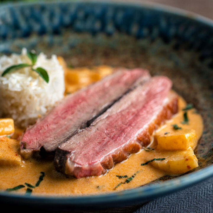 Thai red duck curry with pineapple, rice and Thai basil in a blue bowl.