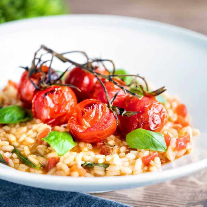 Tomato risotto with basil and balsamic roasted tomatoes served in a white bowl.
