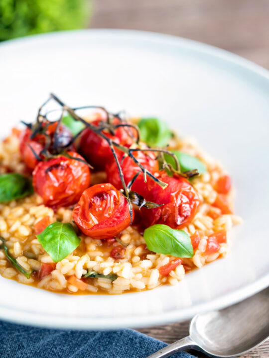 Tomato risotto with basil and roasted tomatoes served in a white bowl.