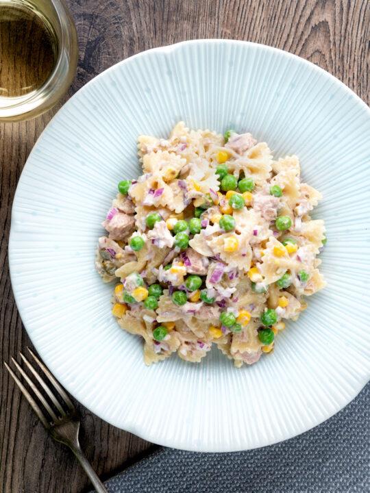 Overhead tuna pasta salad with peas, corn and red oniion.