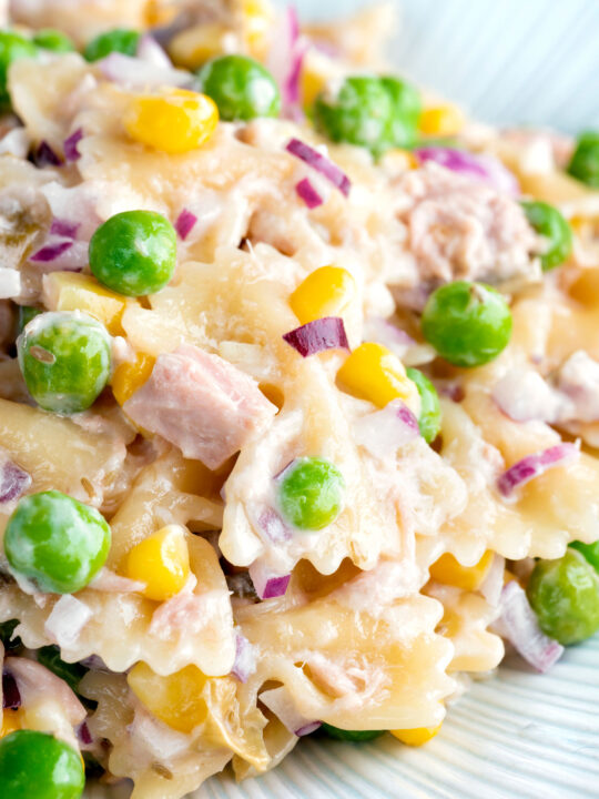 Close up tuna pasta salad with peas, corn and red onion.