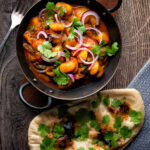 Overhead Indian butter bean curry served with a naan bread featuring a title overlay.