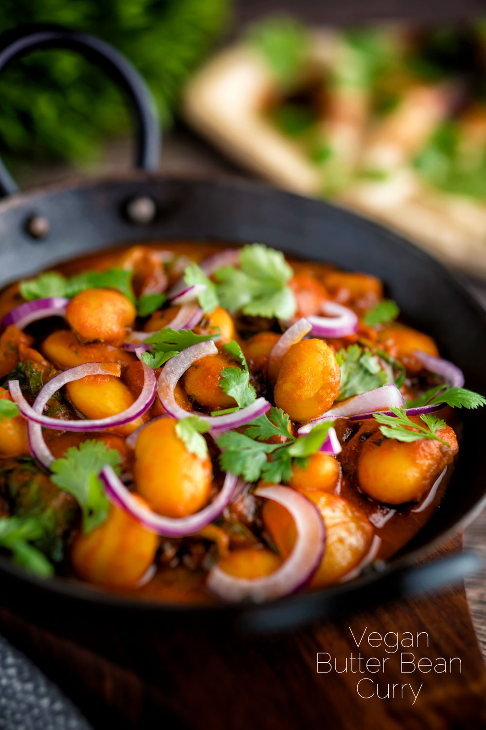 Indian vegan butter bean curry served with coriander and red onion featuring a title overlay.