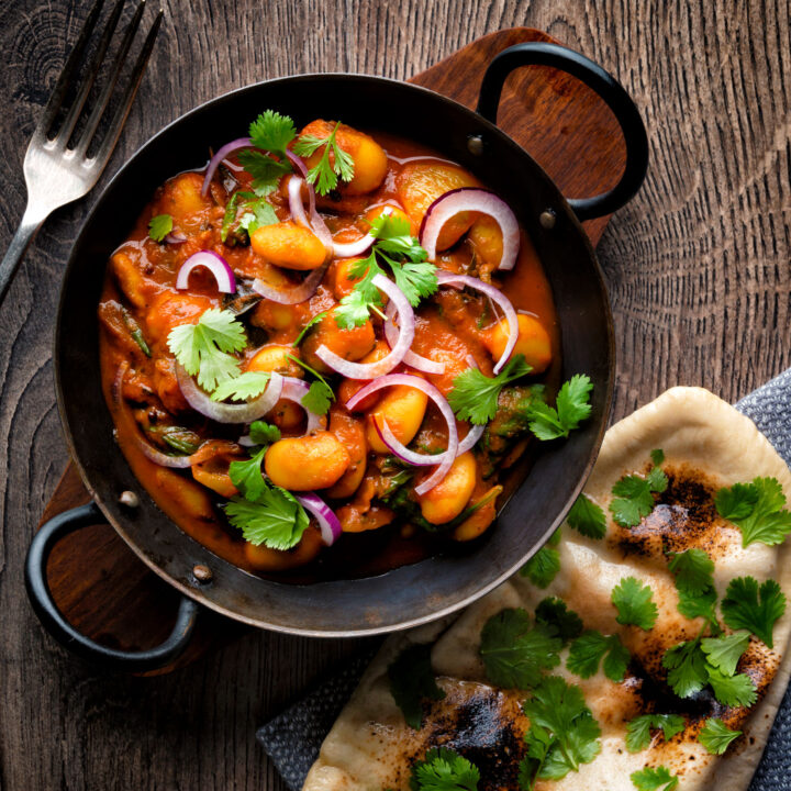 Indian vegan butter bean curry served with coriander, red onion and a naan bread.