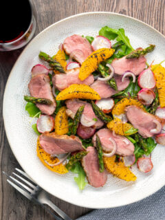 Overhead duck breast salad with roasted radish and asparagus with orange segments.