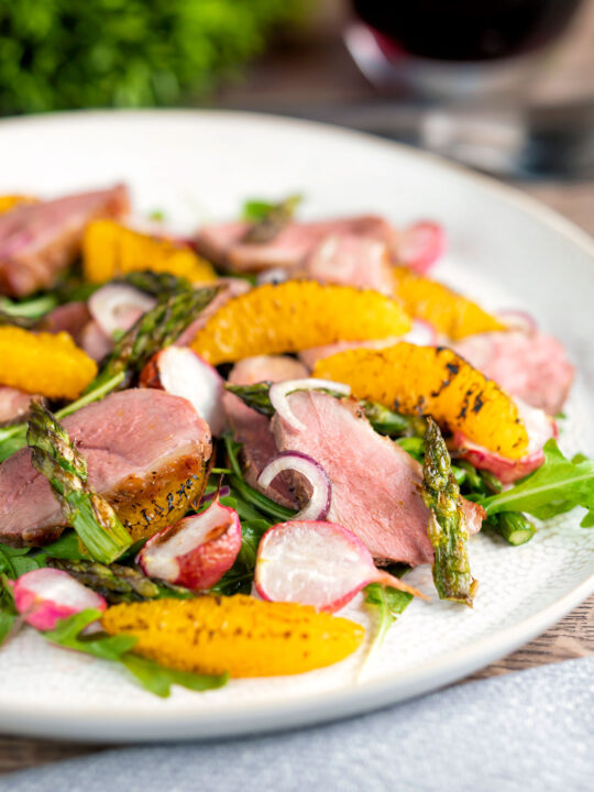 Duck breast salad with rocket, roasted radish and asparagus with orange segments.