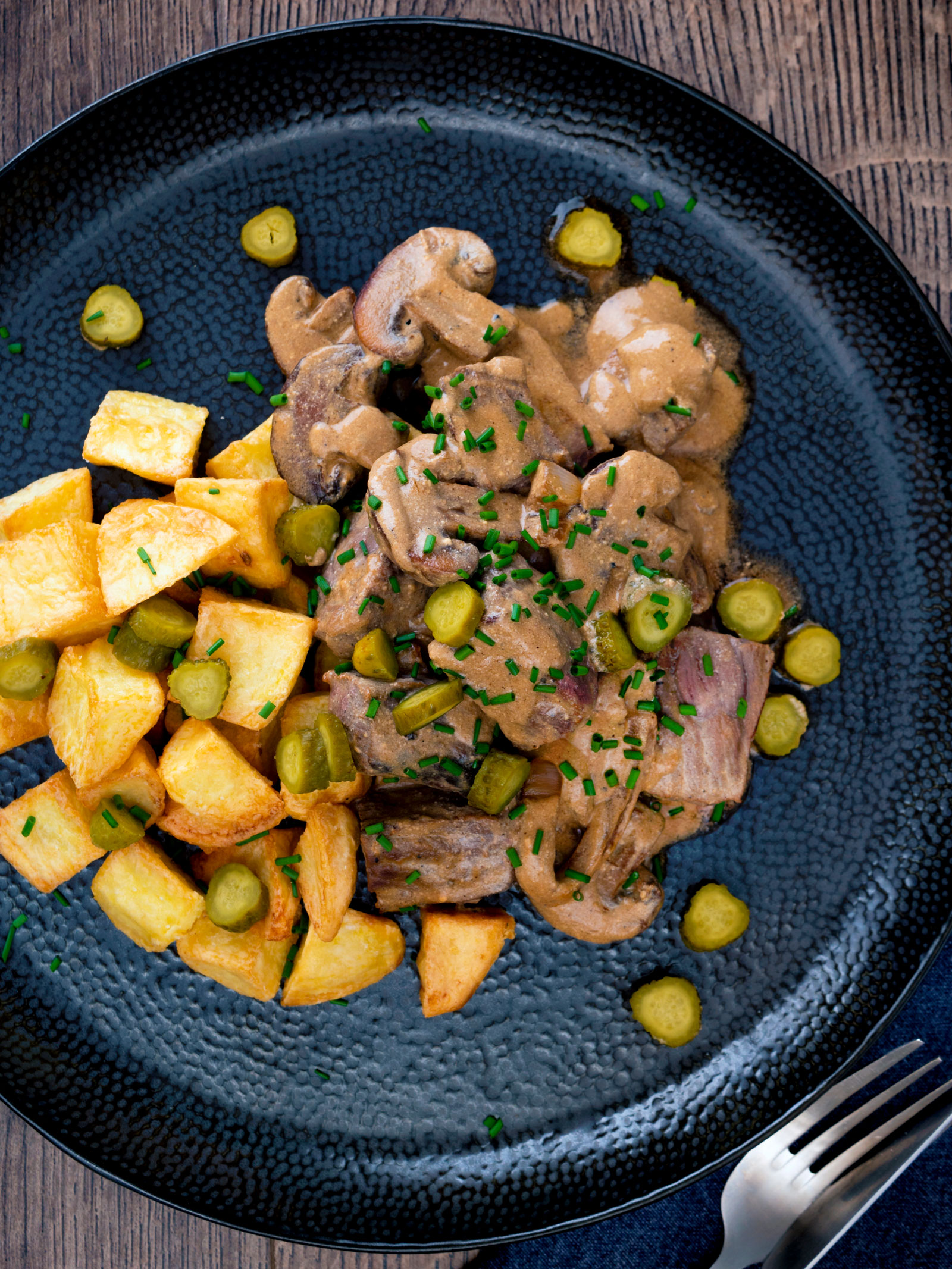 Overhead beef and mushroom stroganoff served with fried potatoes and pickles.