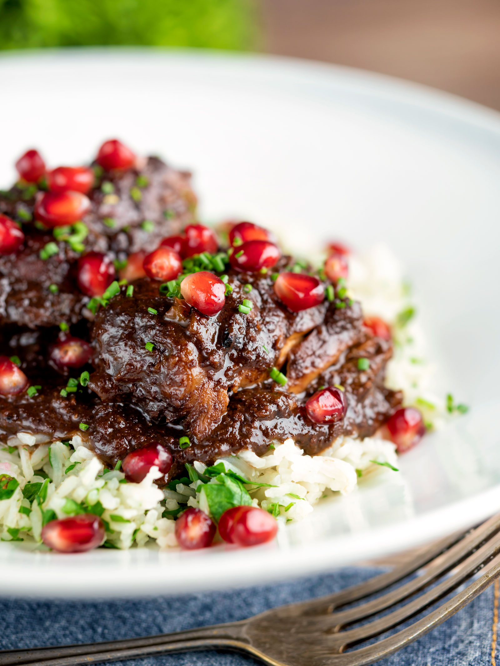 Iranian fesenjan chicken thigh stew with pomegranate served on herbed rice.