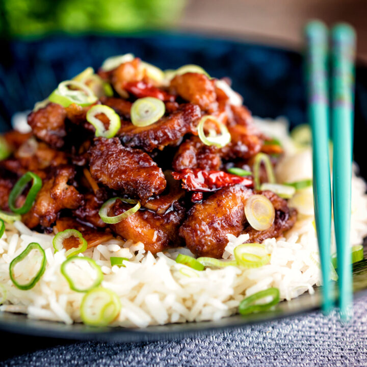 General Tso's chicken fakeaway recipe served on white rice in a blue bowl.