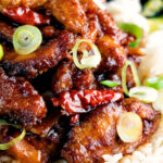 Close up General Tso's chicken fakeaway recipe served on white rice featuring a title overlay.