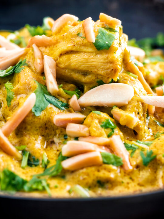 Close up chicken korma curry garnished with coriander and almonds.
