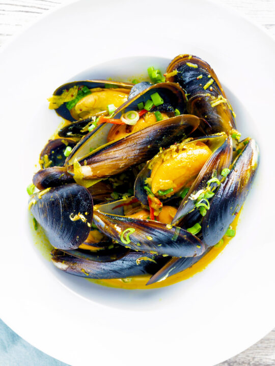 Overhead curry mussels in a coconut milk sauce serve in a white bowl.