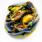 Overhead curry mussels in a coconut milk sauce serve in a white bowl featuring a title overlay.