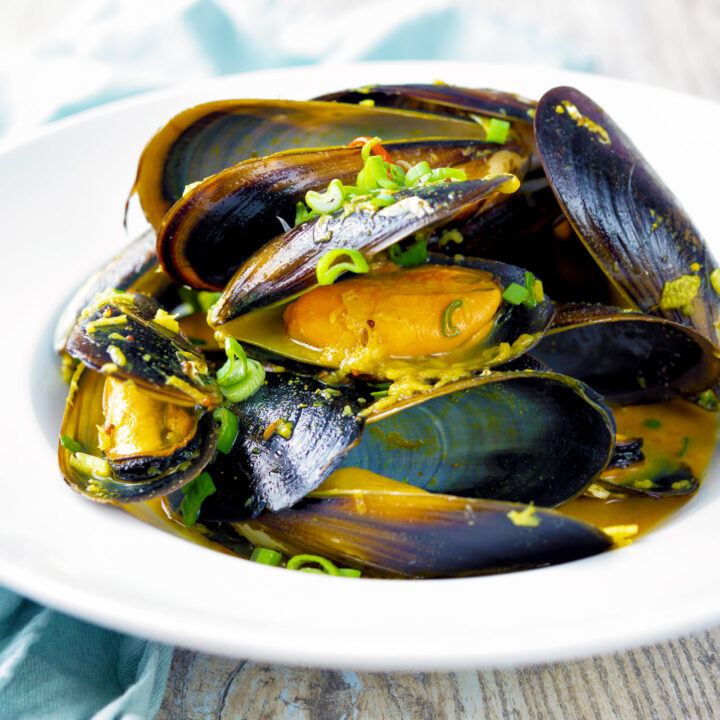 Indian curry mussels served in the shells in a coconut milk sauce.