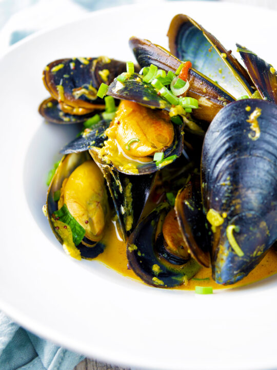Indian curry mussels in a coconut milk sauce serve in a white bowl.