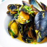 Indian curry mussels in a coconut milk sauce serve in a white bowl featuring a title overlay.