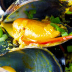 Close up Indian curry mussels in a coconut milk sauce.