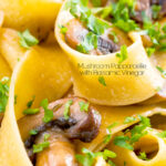 Close up garlic mushroom pappardelle with parsley featuring a title overlay.